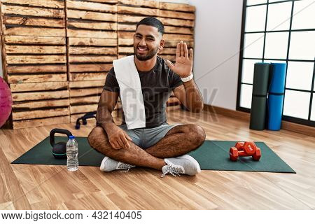 Young indian man sitting on training mat at the gym waiving saying hello happy and smiling, friendly welcome gesture