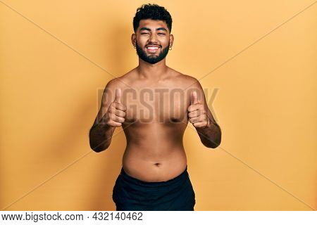 Arab man with beard wearing swimwear shirtless success sign doing positive gesture with hand, thumbs up smiling and happy. cheerful expression and winner gesture.