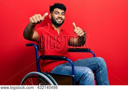 Arab man with beard sitting on wheelchair approving doing positive gesture with hand, thumbs up smiling and happy for success. winner gesture.