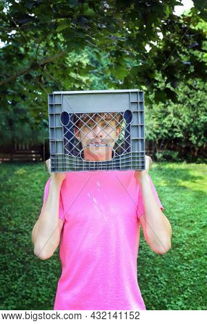 Teen boy holding a milk crate over his head ready for the social media milk crate challenge