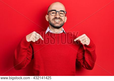 Young bald man wearing casual clothes and glasses looking confident with smile on face, pointing oneself with fingers proud and happy.