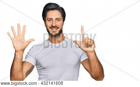 Young hispanic man wearing casual white t shirt showing and pointing up with fingers number seven while smiling confident and happy.