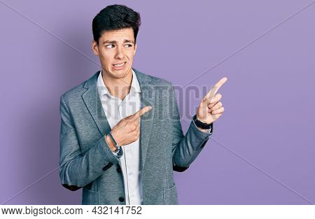 Young hispanic man wearing business clothes pointing aside worried and nervous with both hands, concerned and surprised expression