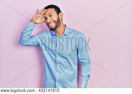 Hispanic man with beard wearing casual blue shirt very happy and smiling looking far away with hand over head. searching concept.
