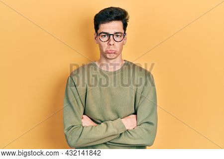 Young hispanic man with arms crossed gesture depressed and worry for distress, crying angry and afraid. sad expression.