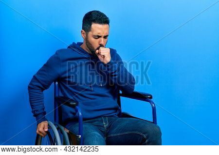 Handsome hispanic man with beard sitting on wheelchair feeling unwell and coughing as symptom for cold or bronchitis. health care concept.
