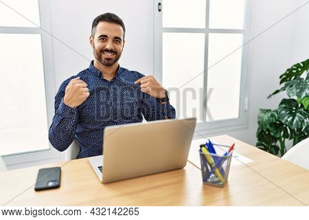 Young hispanic man with beard working at the office with laptop looking confident with smile on face, pointing oneself with fingers proud and happy.