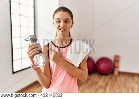 Young brunette teenager wearing sportswear holding water bottle pointing aside worried and nervous with forefinger, concerned and surprised expression