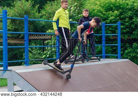 Group Of Boys Ride A Scooter In An Extreme Park. Study Of Extreme Sports On The Open Air.