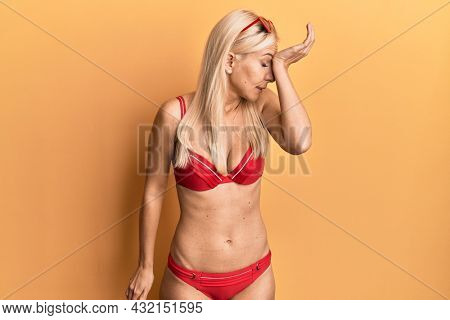 Young blonde woman wearing bikini surprised with hand on head for mistake, remember error. forgot, bad memory concept.