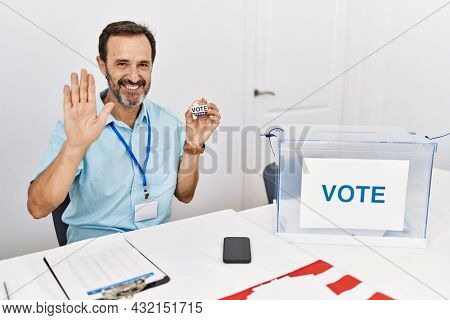 Middle age man with beard sitting by ballot holding i vote badge waiving saying hello happy and smiling, friendly welcome gesture