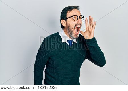 Middle age hispanic man wearing casual clothes and glasses shouting and screaming loud to side with hand on mouth. communication concept.