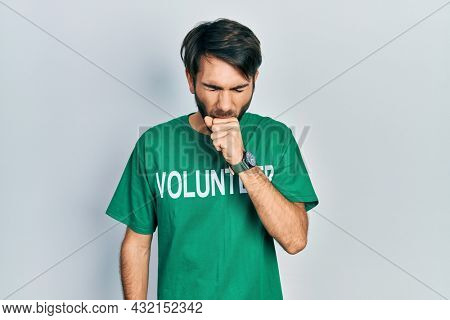 Young hispanic man wearing volunteer t shirt feeling unwell and coughing as symptom for cold or bronchitis. health care concept.