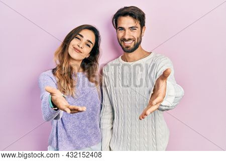 Young hispanic couple wearing casual clothes smiling cheerful offering palm hand giving assistance and acceptance.