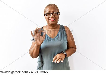 Mature hispanic woman wearing glasses standing over isolated background disgusted expression, displeased and fearful doing disgust face because aversion reaction.