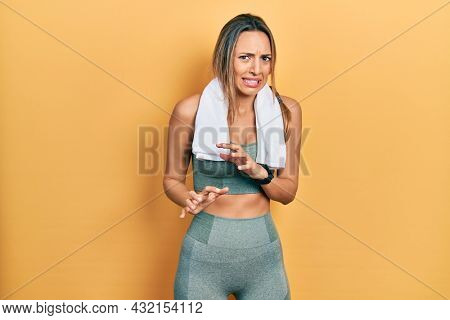 Beautiful hispanic woman wearing sportswear and towel disgusted expression, displeased and fearful doing disgust face because aversion reaction.