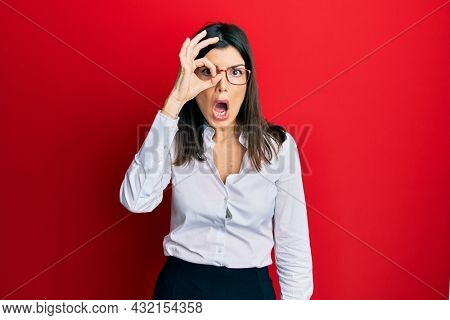 Young hispanic woman wearing business shirt and glasses doing ok gesture shocked with surprised face, eye looking through fingers. unbelieving expression.