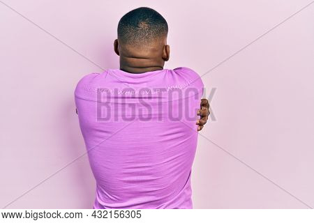 Young black man wearing casual pink sweater hugging oneself happy and positive from backwards. self love and self care