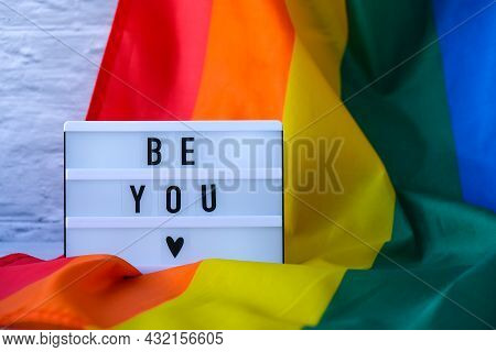 Rainbow Flag With Lightbox And Text Be You. Rainbow Lgbtq Flag Made From Silk Material. Symbol Of Lg