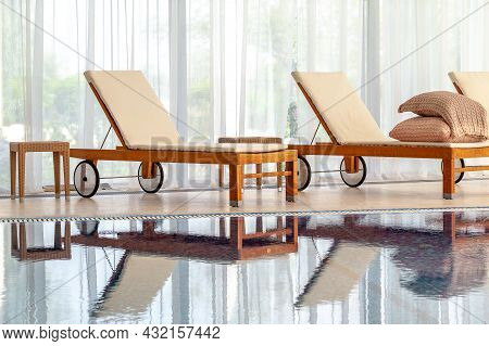 Wooden Chaise Lounges With Mattresses Against Wide Window In Home Indoor Pool