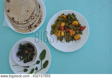 North Indian Food - Matar Paneer Mix Veg, Saag And Roti On White Plate With Light Blue Background