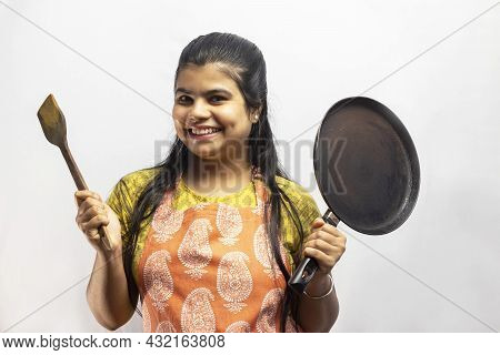 A Pretty Indian Housewife Woman In Cooking Apron With Wooden Spatula And Frying Pan In Hands Smiles