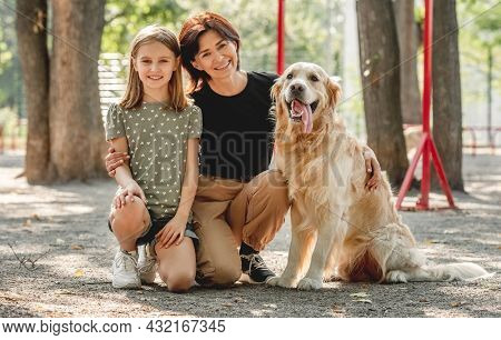 Family with golden retriever dog portrait in the park. Mother, daughter and doggy pet looking at camera together