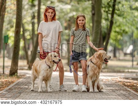 Girls with golden retriever dogs in the park. Sisters walking with pets doggies at nature
