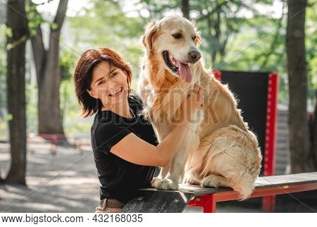 Girl petting golden retriever dog after training and smiling outdoors. Young woman with doggy petportrait in the park together