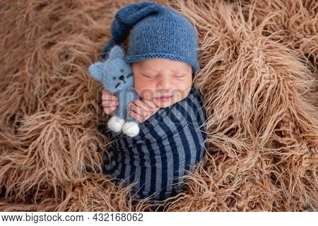 Adorable newborn baby boy swaddled in toby fabric hugging knitted toy and smiling during sleeping. Cute infant kid wearing hat napping in fur during studio photoshoot.