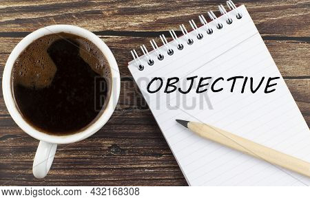Objective Text On Notebook With Coffee On The Wooden Background