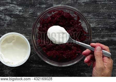 Top View Of Grated Cooked Beet In Glass Bowl And Woman Hand Putting Sour Cream With Spoon Into Salad