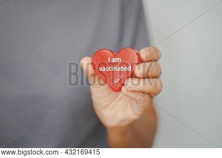 Senior Woman's Hand Showing Red Heart Sharp With I'm Vaccinated Word In Soft Focus,  Due To Spread O