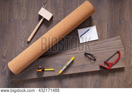 Laminate floor and tools background texture. Wooden laminate floor with cork roll