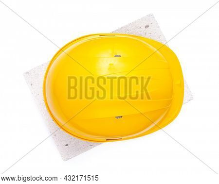 Hardhat at aerated concrete block isolated on white background. Helmet and brick