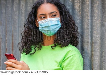 Mixed race biracial African American teenager teen girl young woman wearing a face mask and using mobile cell phone for social media during the Coronavirus COVID-19 pandemic