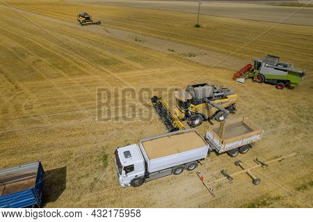 Combine Harvesters Fill Grain Trucks With Wheat Right In The Field. Photo From A Drone. Aerial View.