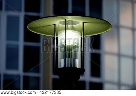 Antique Street Lantern Lights Up At Night In Front Of Blurred Building