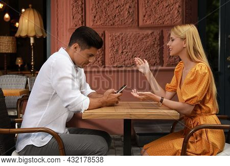 Man With Smartphone Ignoring His Girlfriend In Cafe. Boring Date