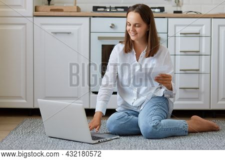 Happy Young Caucasian Woman Sitting On The Floor In Kitchen, Holding Paper Document Or Letter, Check