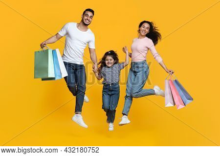 Big Shopping Concept. Overjoyed Arab Family Of Three Jumping With Shopper Bags