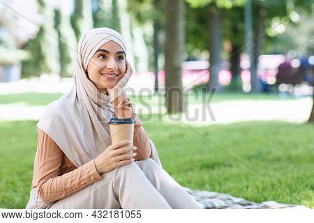 Smiling Millennial Arabian Muslim Woman Student In Hijab Take A Break From Work Or Study, Relax In P