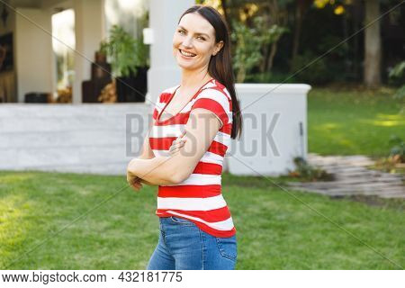 Portrait of smiling caucasian woman outside house looking at camera in garden. spending time at home.