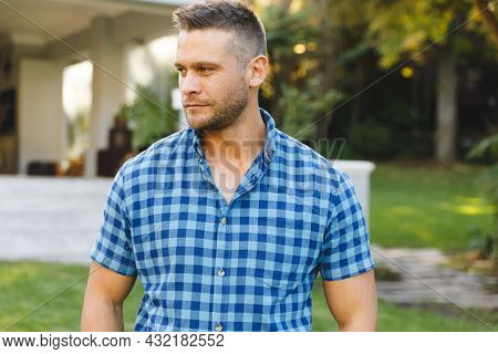 Smiling caucasian man outside house looking away from camera in garden. spending time at home.