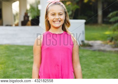 Portrait of smiling caucasian girl outside house looking at camera in garden. spending time at home.