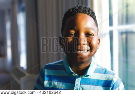 Portrait of african american boy looking at camera and smiling in living room. spending time alone at home.