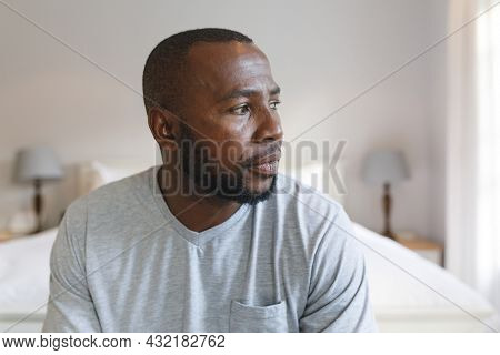 Thoughtful african american man sitting on bed and looking away in bedroom. spending time alone at home.