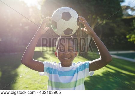Portrait of smiling african american boy having fun and playing with football in garden. family spending time at home. miling