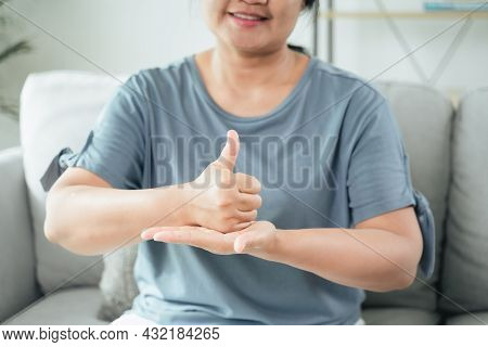 Mature Asian Deaf Disabled Woman Using Sign Language To Communicate With Other People.