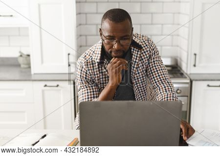 Smiling african american man sitting in kitchen working using laptop. remote working from home with technology.
